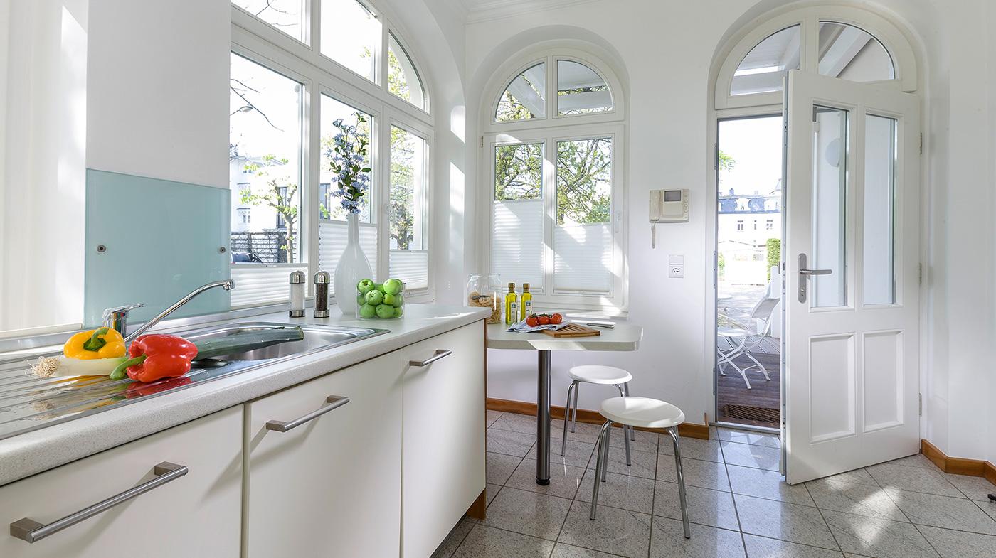 helle Küche mit kleiner Sitzecke und Zugang zur Terrasse