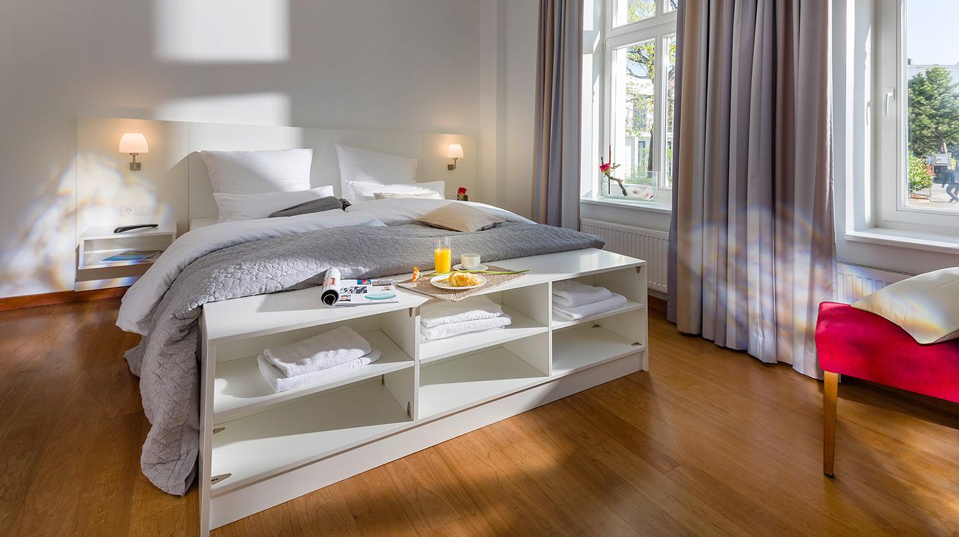 Schlafzimmer mit Doppelbett, Flachbildfernseher und großer Fensterfront