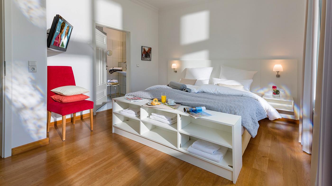 Schlafzimmer mit Flachbildfernseher und Zugang zum Bad