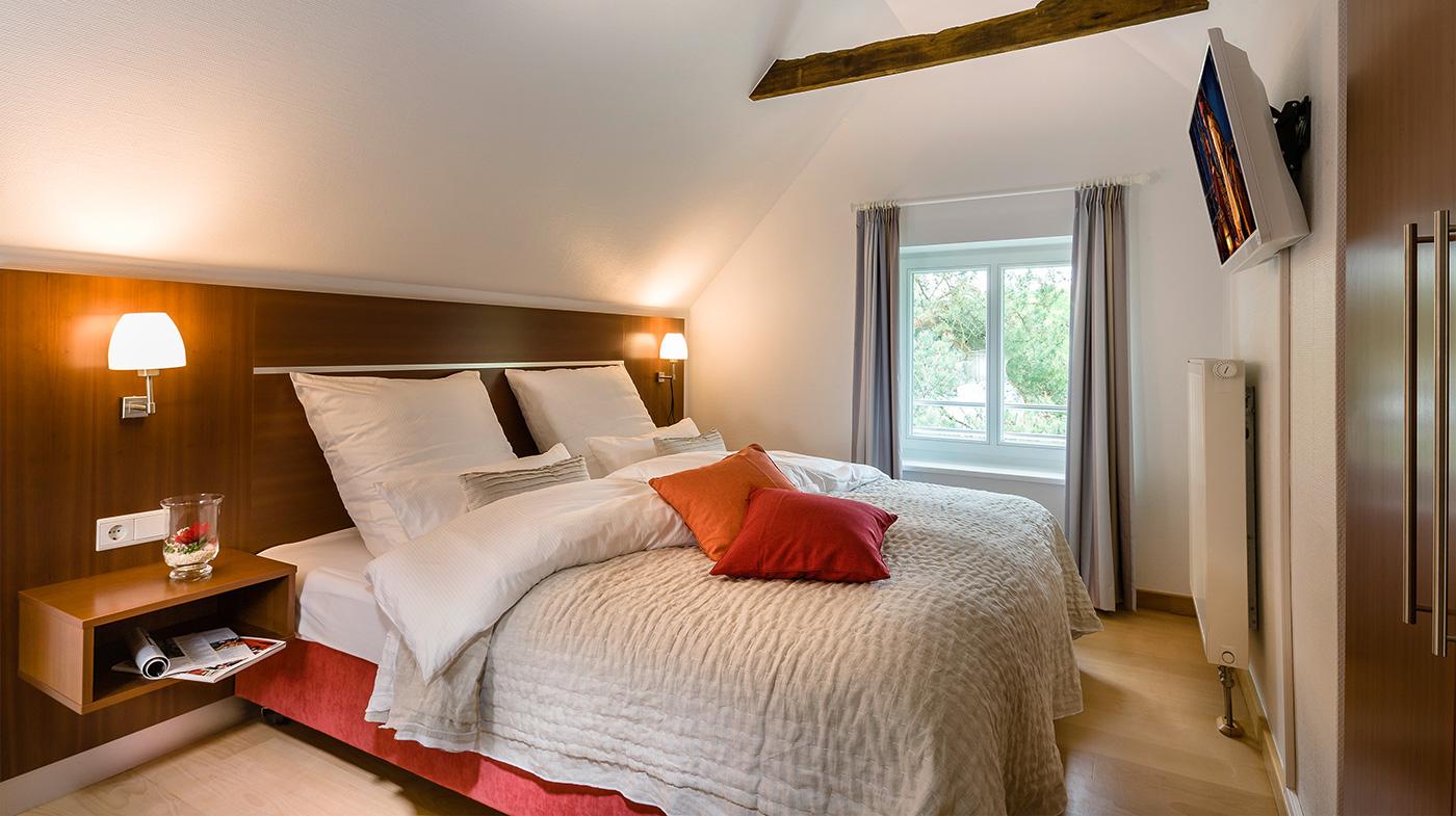 Schlafzimmer mit Doppelbett und Flachbildfernseher
