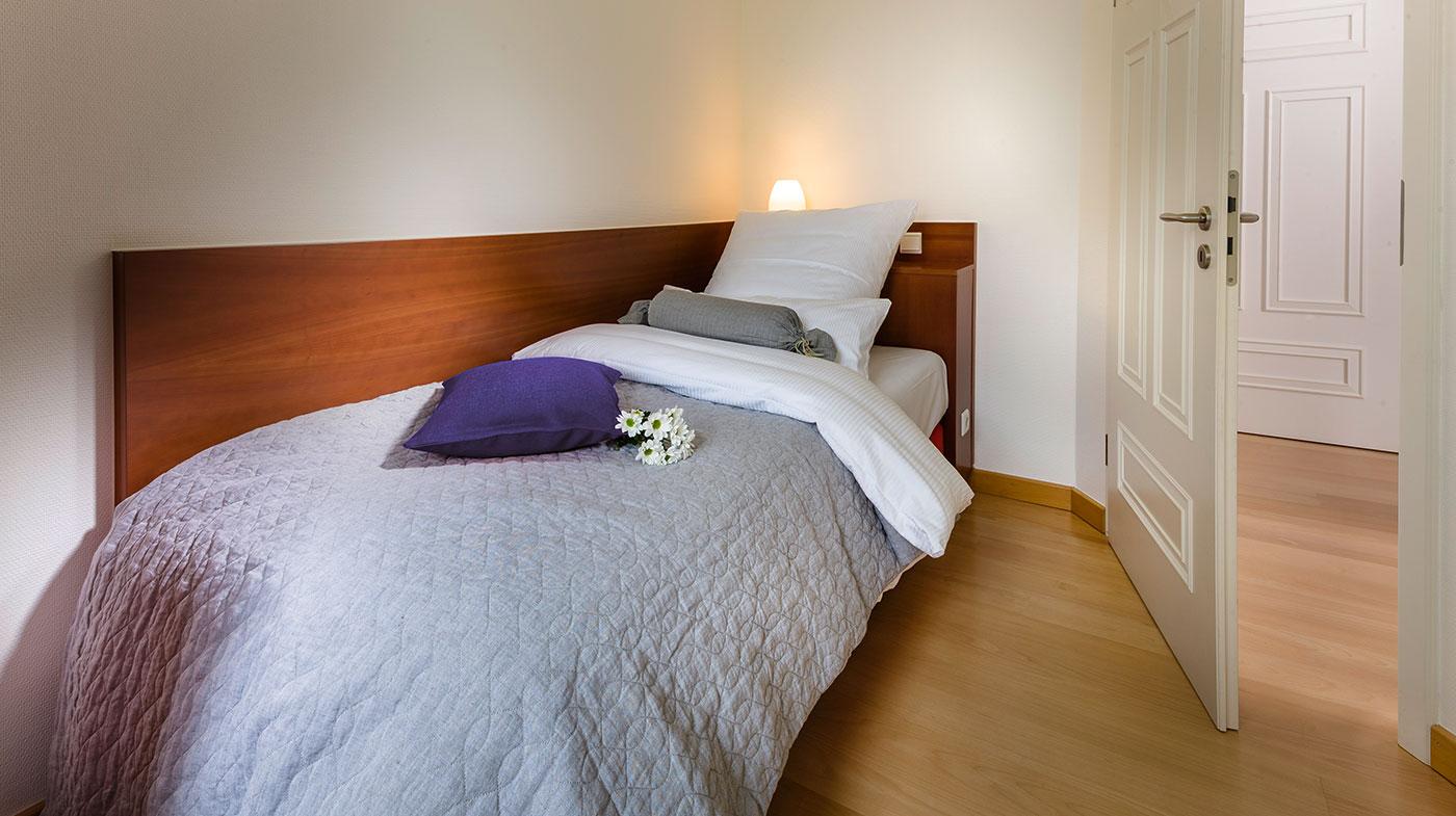 Schlafzimmer mit Einzelbett und Flachbildfernseher