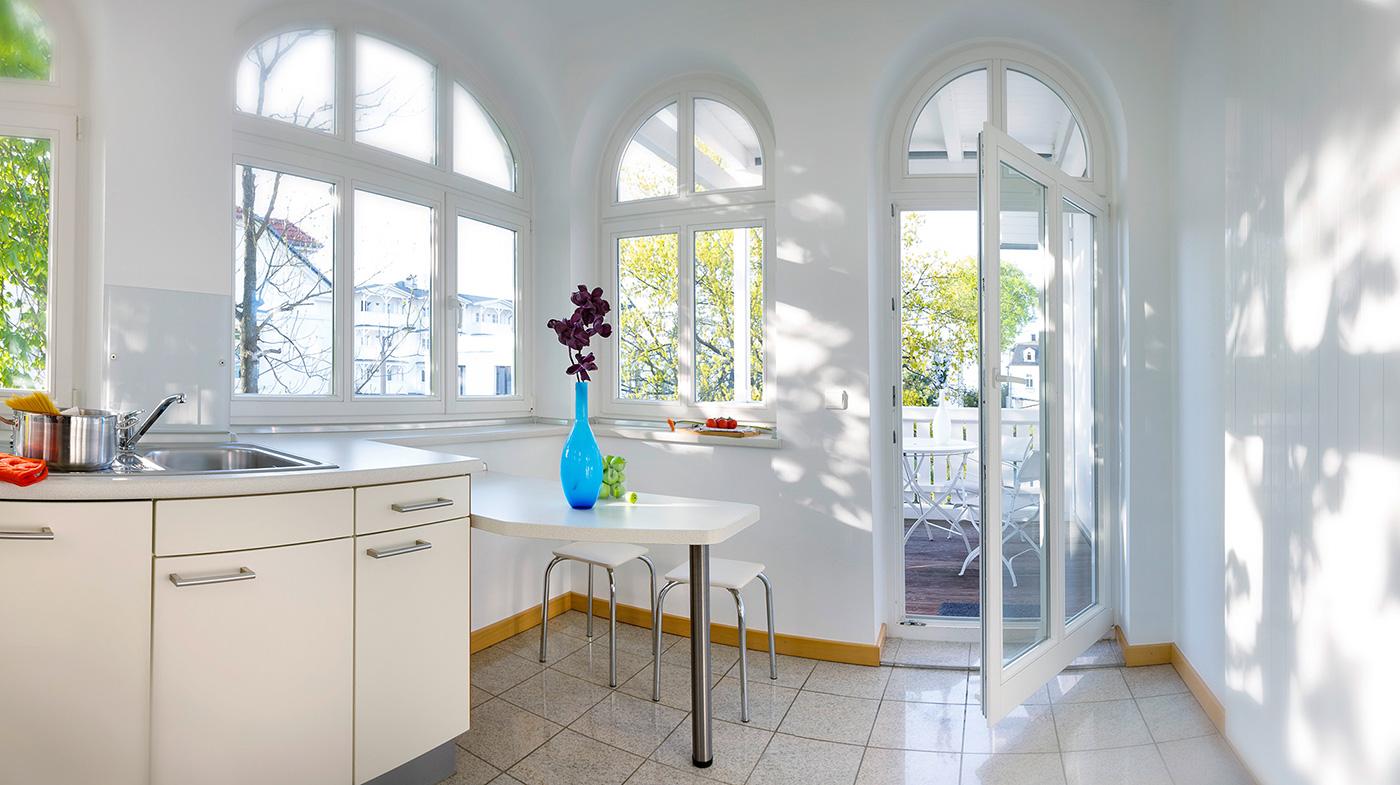 Küche mit kleiner Sitzecke und Zugang zum sonnigen Balkon mit Bistrotisch