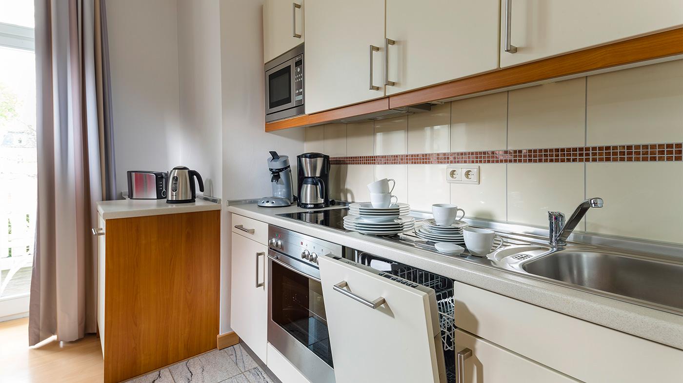 offene Kochzeile mit modernen Geräten und hochwertigem Geschirr