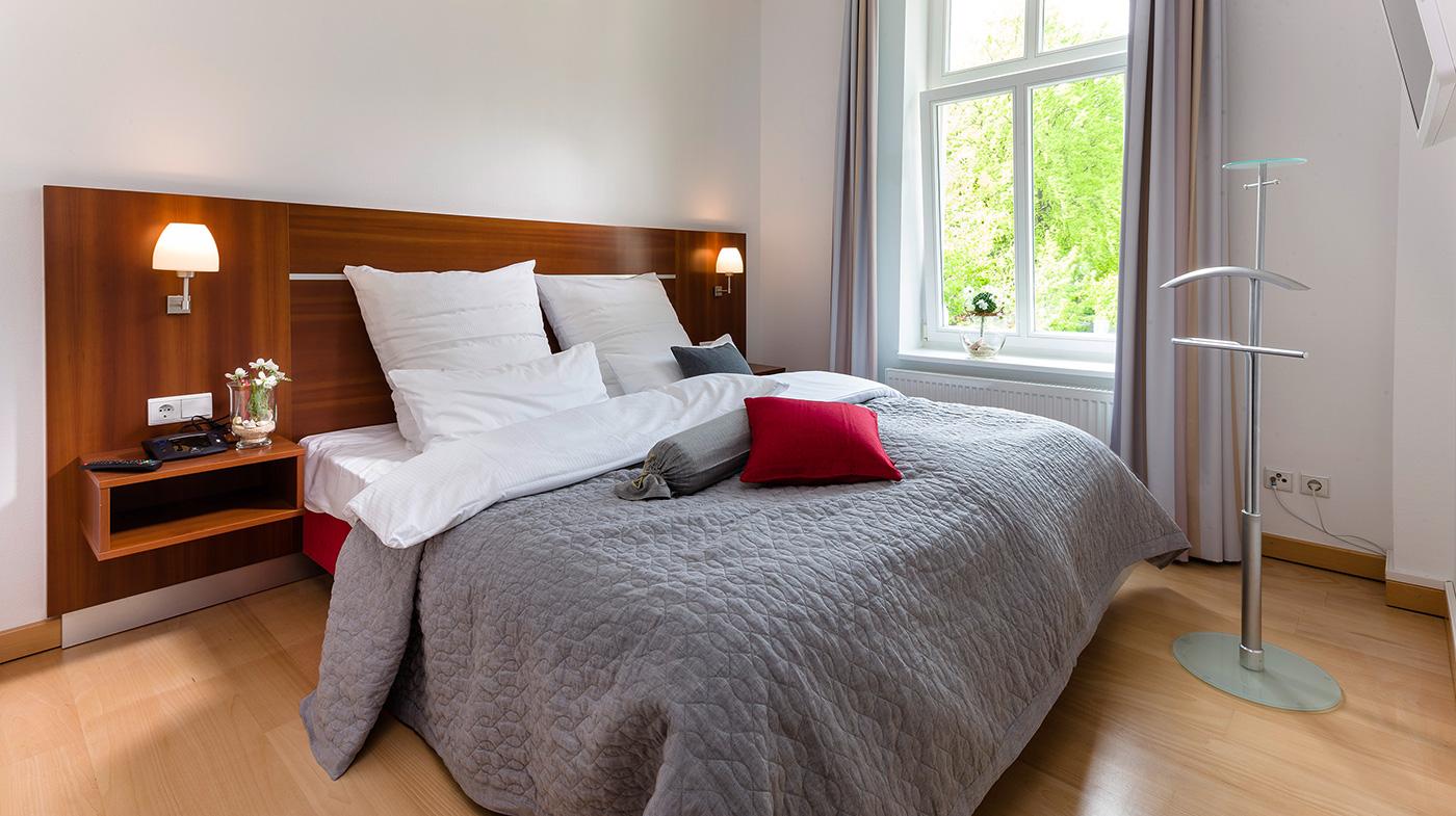 großes Schlafzimmer mit Doppelbett und Flachbildfernseher