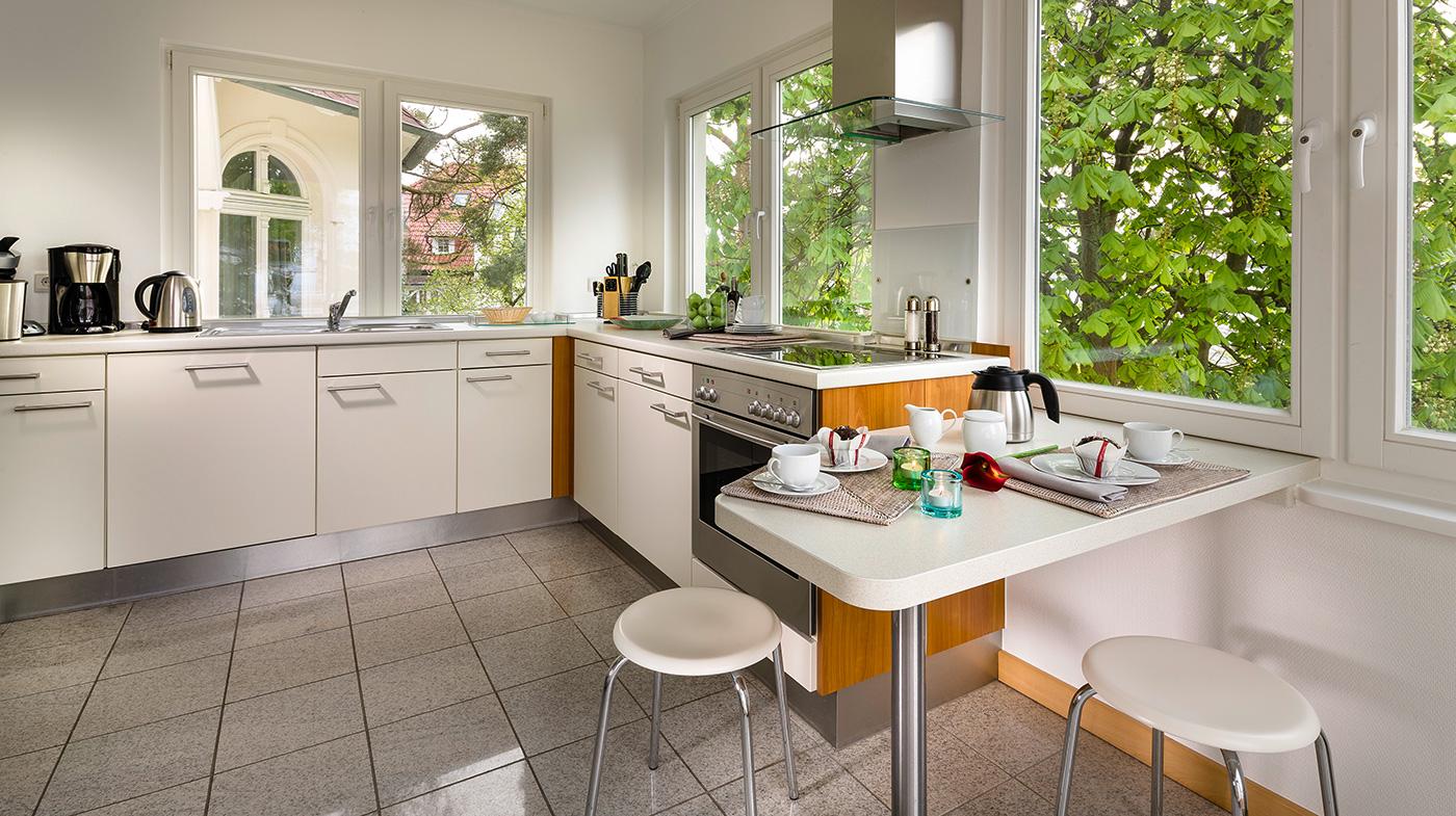 helle Küche mit Vollausstattung und kleiner Sitzecke sowie Zugang zum Balkon